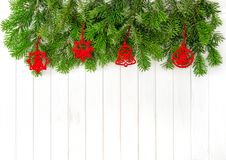 Christmas tree branches red decoration wooden background. Christmas evergreen tree branches red decoration on bright wooden background Stock Photo