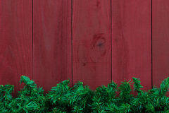 Christmas evergreen tree garland border with antique red wood background stock photo