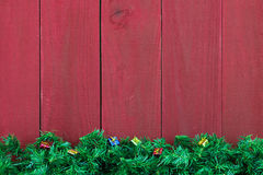 Christmas evergreen tree garland border with presents by antique red wood background Stock Images