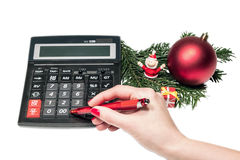 Christmas expences. Woman hand calculating near Christmas decorations Stock Photos