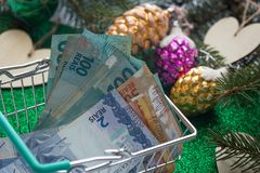 Christmas expenses / concept / Brazilian money, reais in the shopping cart and holiday decorations Royalty Free Stock Photo