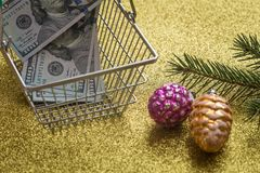 Christmas expenses / holiday decortions and United States dollars in the shopping cart / concept Royalty Free Stock Images