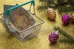 Christmas expenses / holiday decortions and Euro money in the shopping cart / concept Royalty Free Stock Photography