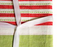 Christmas fabric and ribbon. Close-up of a Christmas gift wrapped in fabric and ribbon - traditional red and green Stock Image
