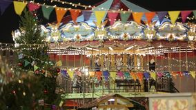 Christmas Fair. Multicolored carousel is spinning in amusement park, Holiday. stock video