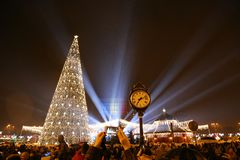 Christmas fair night 2017 at Bucharest, Romania. Constitution Square - fir and rays of light in the night rain Stock Image