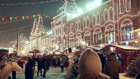 Christmas fair on Red Square in Moscow, GUM at background. Christmas fair on Red Square. Pedestrians passing by, slightly blurred GUM at background stock video footage