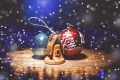 Christmas fairy composition of Christmas decorations: two balls and a clay house under artificial snow royalty free stock images