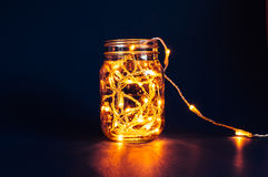 Christmas fairy lights in a mason jar. Glowing in the dark, on a blue background Royalty Free Stock Photos