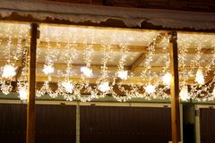 Christmas fairy lights under roof. Christmas fairy lights under the snowy pavilion roof Royalty Free Stock Images