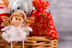 Christmas fairy sitting in a basket with balls and gifts. Decorations on the Christmas tree Stock Images