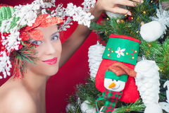 Christmas fairy woman with tree hairstyle decorating christmas tree Stock Images