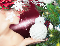 Christmas fairy woman with tree hairstyle decorating christmas tree Royalty Free Stock Photography