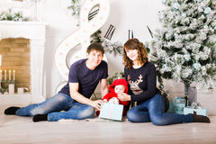 Christmas Family with baby opening gifts. Happy Stock Photo