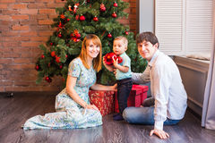 Christmas Family with child. Happy Smiling Parents and Children at Home Celebrating New Year. Christmas Tree. Stock Photography