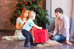 Christmas Family with child. Happy Smiling Parents and Children at Home Celebrating New Year. Christmas Tree. Stock Photo