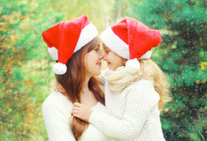 Christmas family child hugging mother in santa red hats together over tree Royalty Free Stock Photos