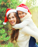 Christmas family child hugging mother in santa red hats together over tree having fun Stock Image