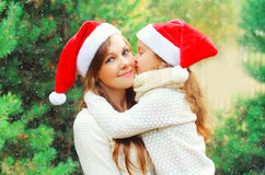 Christmas family child kissing mother in santa red hats together over tree. Christmas family child kissing mother in santa red hats together over a tree Royalty Free Stock Photography