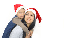 Christmas, family, childhood and people concept - happy mother and little girl in santa hats over holidays isolated Stock Photography