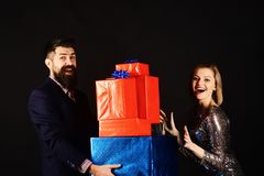 Christmas family concept. Couple in love holds stack of presents. On black background. Girl and bearded men with cheerful faces and red and blue gift boxes stock photos