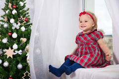 Christmas and family concept - little girl and decorated Christm Stock Images