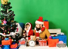 Christmas family decorates fir tree on green background. Boy and men with beard and curious faces put Christmas ball on tree. Family holidays concept. Santa royalty free stock image
