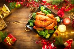 Christmas family dinner. Roasted chicken on holiday table, decorated with gift boxes, burning candles and garlands stock images