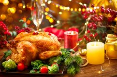 Christmas family dinner. Roasted chicken on holiday table, decorated with gift boxes, burning candles and garlands. Roasted turkey royalty free stock image