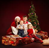 Christmas family, fir tree with gift boxes. Christmas family of four persons and fir tree with gift boxes over red background Royalty Free Stock Images