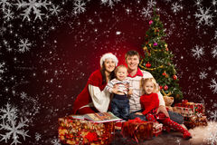 Christmas family, fir tree with gift boxes. Christmas family of four persons and fir tree with gift boxes over red background Stock Photos