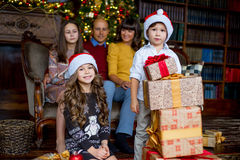 Christmas family of five people, happy parents and their kids. With gifts. First plan of boy and girl. Christmas and New Year interior Stock Images