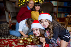 Christmas family of five people, happy parents and their kids. With gifts. First plan of two girls lying on the carpet. Christmas and New Year interior Stock Photo
