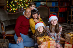 Christmas family of five people, happy parents and their kids. With gifts. First plan of two girls. Christmas and New Year interior Stock Image