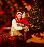 Christmas family fun. Happy father and child hugging near fir tr Royalty Free Stock Photos