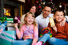 Christmas - family with gifts on Xmas Eve. Christmas - happy family (parents with son and daughter) with gifts on Xmas Eve Royalty Free Stock Images