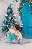 Christmas family at homely cozy house posing close to new-year tree colored in blue. Beautiful woman with cute baby daughter in royalty free stock photos
