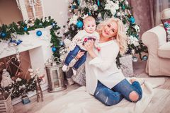 Christmas family, mother and baby smiling near the Xmas tree. Living room decorated by Christmas tree and present gift box royalty free stock photos