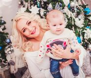 Christmas family, mother and baby smiling near the Xmas tree. stock photography