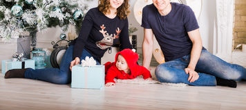 Christmas Family Open Present Gift Box, Mother Father and Baby Child in Decorated Room, sitting under Christmas Tree. Stock Photos