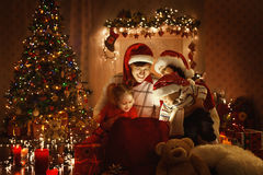 Christmas Family Open Present Gift, Xmas Tree Lights Interior Royalty Free Stock Photography