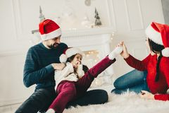 Christmas family paying on home. Mom,Daughter and dad having fun stock image