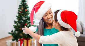 Happy mother and daughter in santa hats. Christmas, family and people concept - happy mother and daughter in santa hats over home background stock images