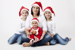 Christmas family portrait. CHristmas portrait of mother, son and twin girls with  christmas caps in a studio Royalty Free Stock Image