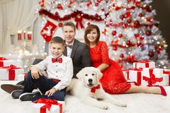 Christmas Family Portrait, Happy Father Mother Child Boy and Dog. Celebrating New Year, people formal dressing suit and dress, decorated Xmas Tree royalty free stock image