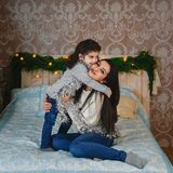 Christmas family portrait of happy smiling mother sitting on bed and hugging small daughter near to christmas tree at home. Winter Royalty Free Stock Photo