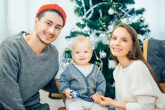 Portrait of friendly family looking at camera on Christmas evening. Christmas Family Portrait In Home Holiday Living Room, Kids and Baby at Santa Hat With Stock Photography