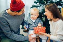 Portrait of friendly family looking at camera on Christmas evening. Christmas Family Portrait In Home Holiday Living Room, Kids and Baby at Santa Hat With Royalty Free Stock Images