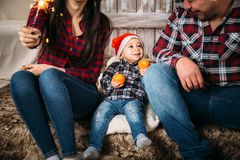 Christmas family portrait of little kid in red santa hat with oranges in hands sitting between parents. Winter holiday Xmas. And New Year concept royalty free stock photography