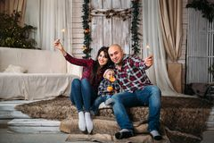Christmas family portrait of young happy smiling parents with little kid in red santa hat holding sparklers. Winter holiday Xmas a. Nd New Year concept royalty free stock photos